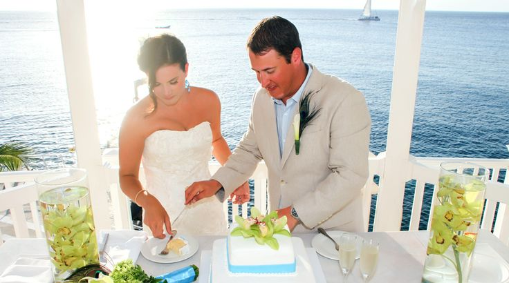 A classic vanilla cake topped with green orchids from this Exotic Peacock themed wedding at Cozumel Palace