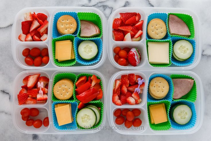 """Lunchable"": crackers, ham, cheese, cucumbers, tomatoes, strawberries.  The one without ham has sweet red peppers, and the one with the biggest appetite got an extra cheese.  Packed in  Easy Lunchboxes , with  square silicone muffin cups. , and little  Minnie Mouse bento forks."