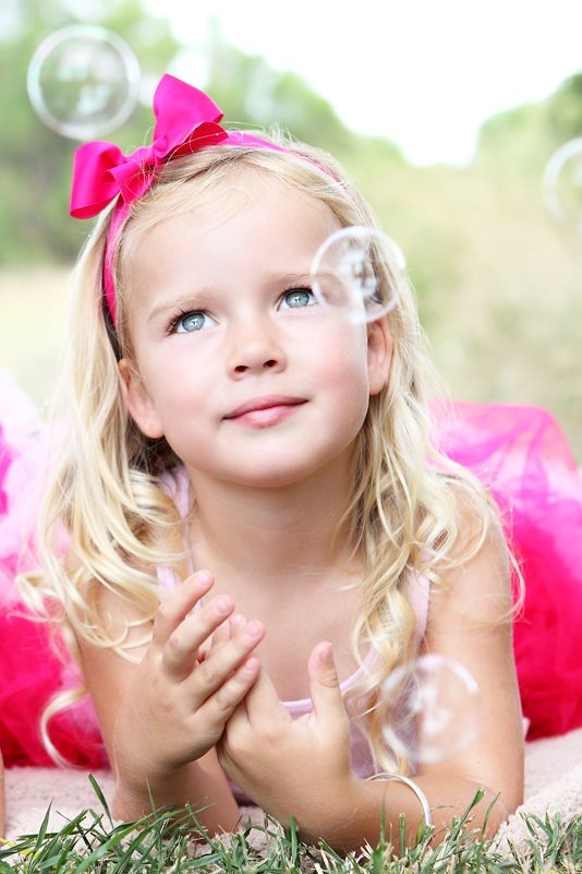Pretty girl with pink bow & bubbles. Great outdoor shot. Child Photography