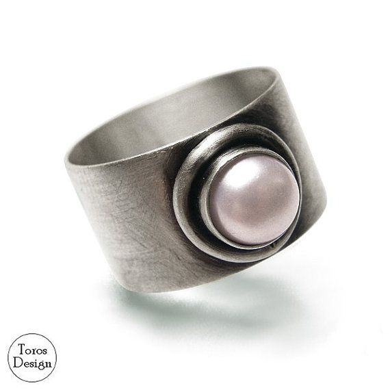 Wide ring with pearl. Handcrafted with sterling silver. The silver is oxidated and matt.  Width: approx. 12 mm. Pearl size: approx 8 mm.