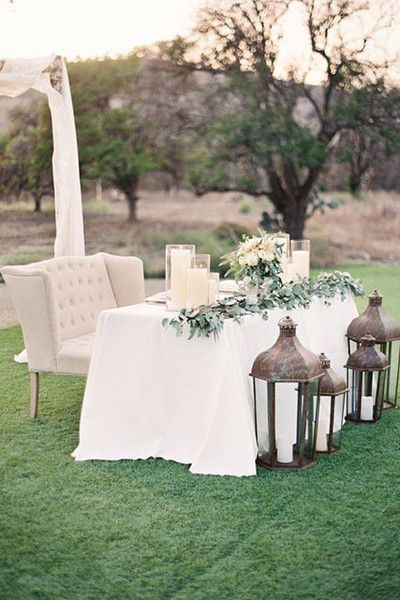 I love the idea of having an outdoor wedding with lots of mismatched, vintage-looking furniture. This sweetheart table with a little couch is so cute!