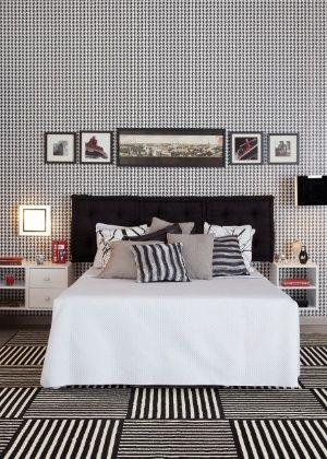 O dormitório de casal, projetado pelo arquiteto Gustavo Calazans, explora os grafismos em preto e branco no tapete listrado e no papel de parede de motivo pied de poule. A utilização do futon preto como cabeceira da cama é uma solução econômica e confortável. A combinação P&B, sempre em alta, confere requinte e modernidade a qualquer ambiente