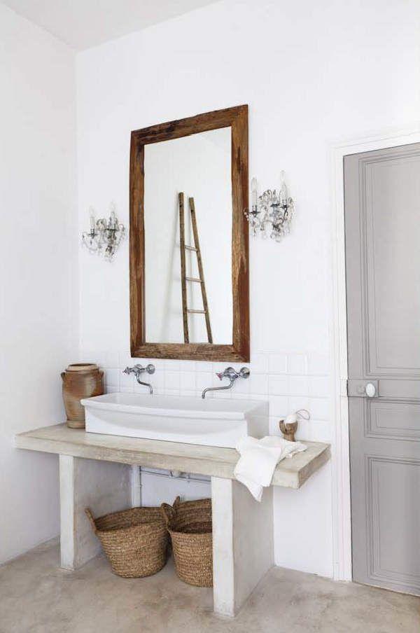 baño, lavabo sobre mueble de obra y suelo con acabado microcemento, grifos de pared, espejo reutilizado