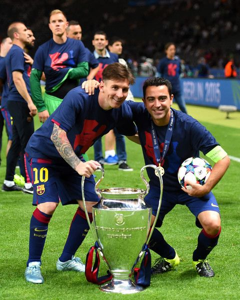 Lionel Messi and Xavi Hernandez of Barcelona celebrate with the trophy after the UEFA Champions League Final between Juventus and FC Barcelona at Olympiastadion on June 6, 2015 in Berlin, Germany.