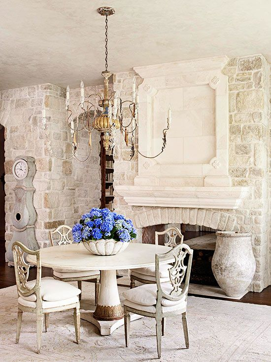 This neutral dining room is simple in color but intricate in design. The monochromatic color scheme is made more interesting with different shapes, positions, and textures on the stone-covered wall. Texture is also added to the room in the subtle design on the rug and the patina of the chairs and table. A grandiose chandelier and bronze-color detailing on the base of the table add an elegant shimmer.