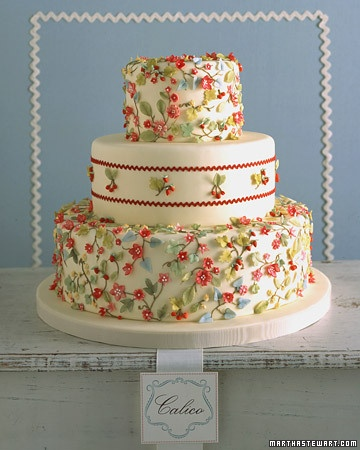 Ambiance~  Calico Wedding Cake  A calico print comes to life on a cake with diminutive hand-sculpted flowers, leaves, and fruits;  Real rickrack trim, bordering clusters of fruit on the middle tier, imparts a cheery, homespun feel. Set against ivory fondant, strawberries & cherries grow from stems of piped royal icing, tinted brown. The fruits are shaped from sugar paste~  (Photo credit: Anna Williams; marthastewart.com)  (410) 819-0046  www.maryannjudy.com
