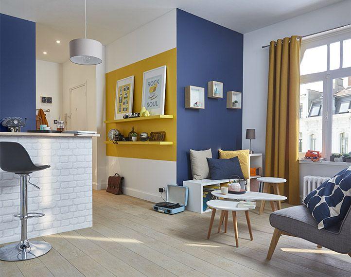 """Inspiration Déco """"Nordique coloré"""" pour ce studio où les couleurs ont été utilisées de façon à délimiter visuellement les espaces, Un aplat jaune pour l'entrée et du bleu pour le salon et le coin cuisine.  On mise sur des rideaux et coussins graphiques aux couleurs coordonnées aux murs pour rester dans le ton !"""