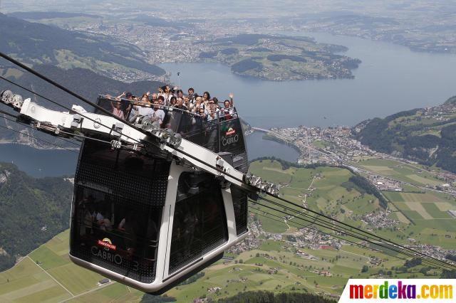 """Penumpang menikmati perjalanan mengenakan kereta gantung bertingkat yang baru dibangun """"Cabrio"""", di gunung Stanserhorn, dekat Lucerne, Swiss."""