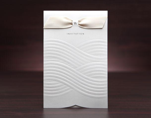Ett av flera nya kort i sortimentet! Ett naturvitt inbjudningskort med ett vågigt mönster och en vacker rosett i champagne. Se detta och fler av våra vackra inbjudningskort på www.Exklusivia.se. #brollopskort #inbjudningskort #exklusivia.se #exklusivia