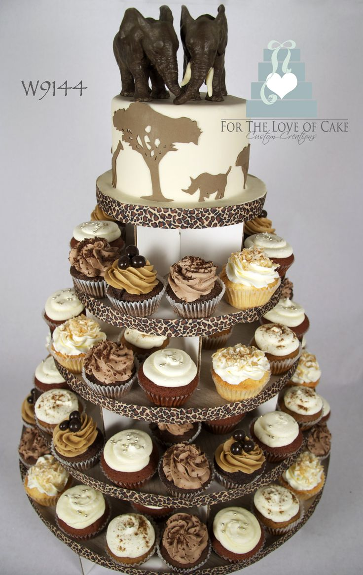 "Safari theme cupcake tower - A 6"" round Safari theme cake with hand-made, modelling chocolate elephants atop a cupcake tower."