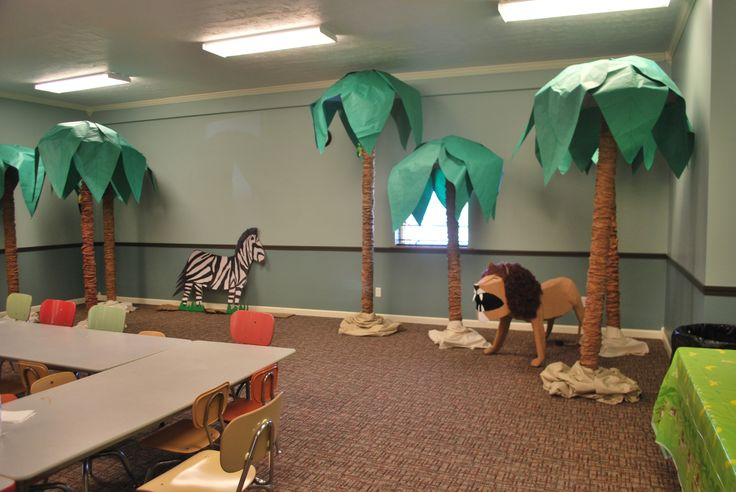 Jungle trees made from carpet tubes, brown lunch bags, umbrellas and green paper. Add a paper mache lion and a cut out zebra and you have our Canopy Café snack area for Jungle Jaunt
