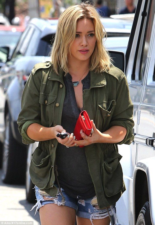 Casual chic: Hilary sported an olive green jacket with the sleeves rolled up, over a grey top and ripped denim shorts