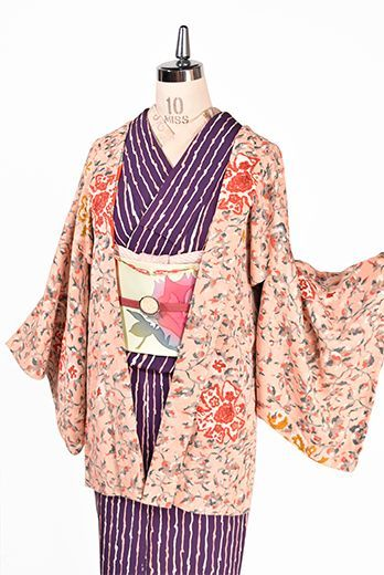 ローズピンクをほのかにおびたはんなりとやわらかなベージュをベースにエロール・ル・カインのいばら姫の絵本を彩るようなエキゾチックな詩情とロマンチックな物語を感じさせてくれる花アラベスク模様が染め出された綸子縮緬のアンティーク羽織です。