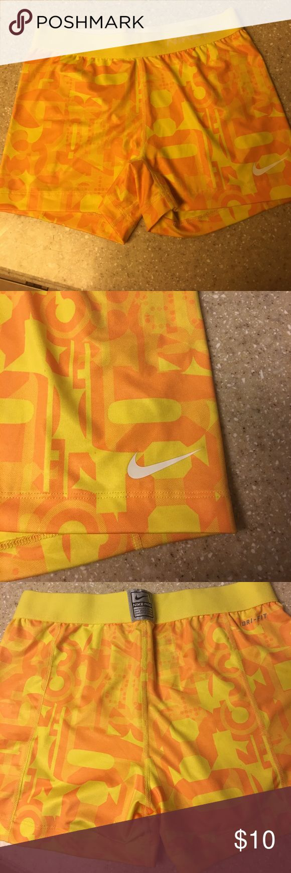 Nike cycle style shorts Dri Fit fluorescent yellow and orange. Super cute Nike Pro workout/running shorts.  Says Large 12/14 but runs very small. I am a size 2 or 3 in jeans. Nike Shorts