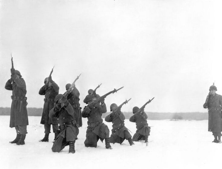 Rifle squad fires volley at the memorial ceremony which was held on 22 January, 1945 for the men who were killed during the siege of Bastogne, Belgium. These men were attached to Company C, 9th Armored Engineer Battalion, 9th Armored Division.