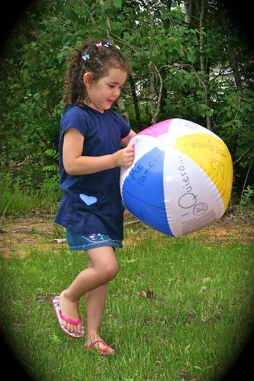 Spanish games for kids using a beach ball.