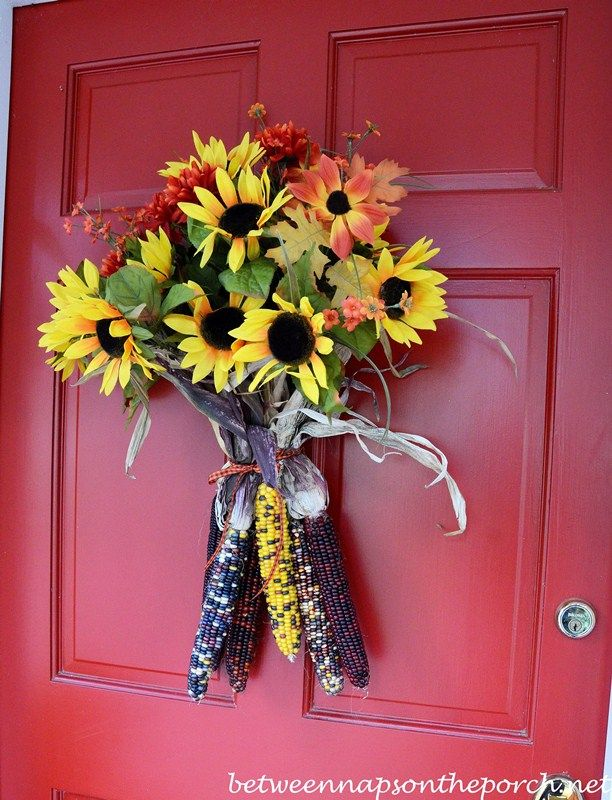 Susan from Between Naps on the Porch created this fresh, easy fall door arrangement by wiring Indian corn around the stems of fall flowers. Looks cheerily autumnal!
