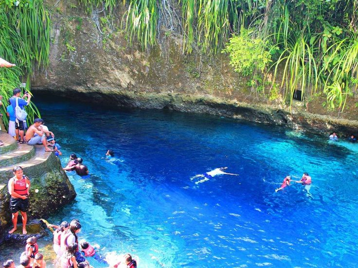 """Surigao del Sur, Philippines - Dive into the clear blue water of the Hinatuan River on the Philippine island of Mindanao. The saltwater river is nicknamed the """"Enchanted River"""" because it appears to run from the middle of nowhere, and is ideal for snorkelers and divers."""