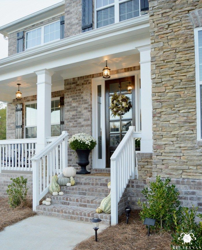 Kelley Nan: Best of Fall: Decorating Ideas & Inspiration- Craftsman style brick home with classy, neutral fall entry with white pumpkins and gourds and white mums in black urns on the front porch.