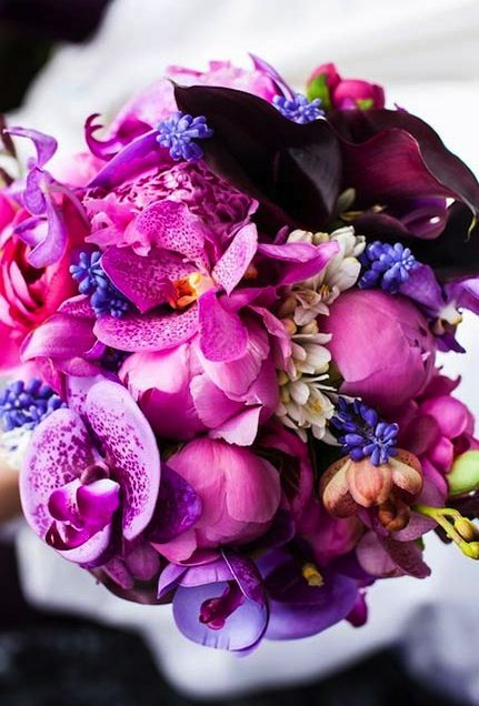 Pump up the flower power with an alluring arrangement of orchids, roses, ranunculus and peonies in shades of pink and purple. #RadiantOrchid #Weddings