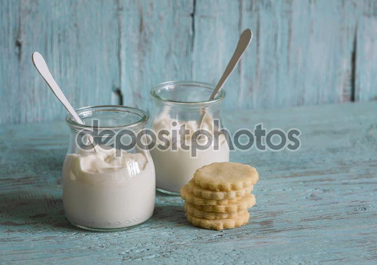 Греческий йогурт в стеклянных банках и песочное печенье на синей деревянной поверхности — стоковое изображение #85126876