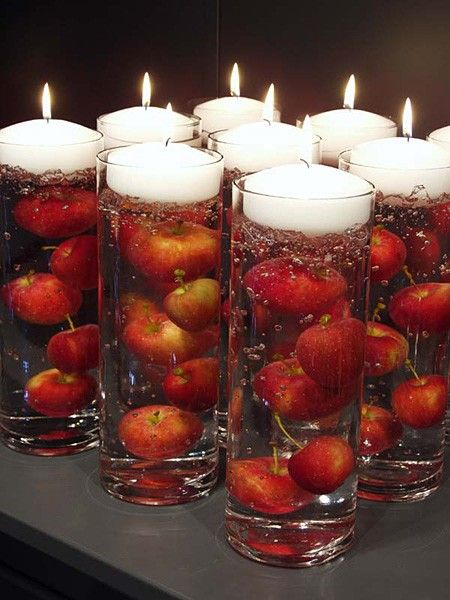 Fill glass cylinders with baby apples or other fruit and place floating candle on top