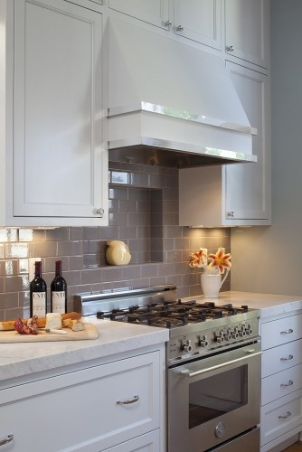 White marble countertops with grey subway tile splash.  Love the inset shelf above the range.  Also, love the hood.