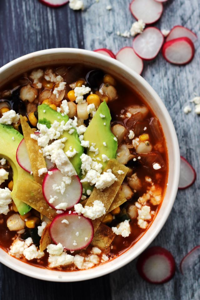 This loaded vegetarian tortilla soup is filled with smoky poblano flavor, hominy, corn, and black beans and then topped with all the best fixins', including avocado, crispy tortilla strips, sliced radish, and queso fresco.