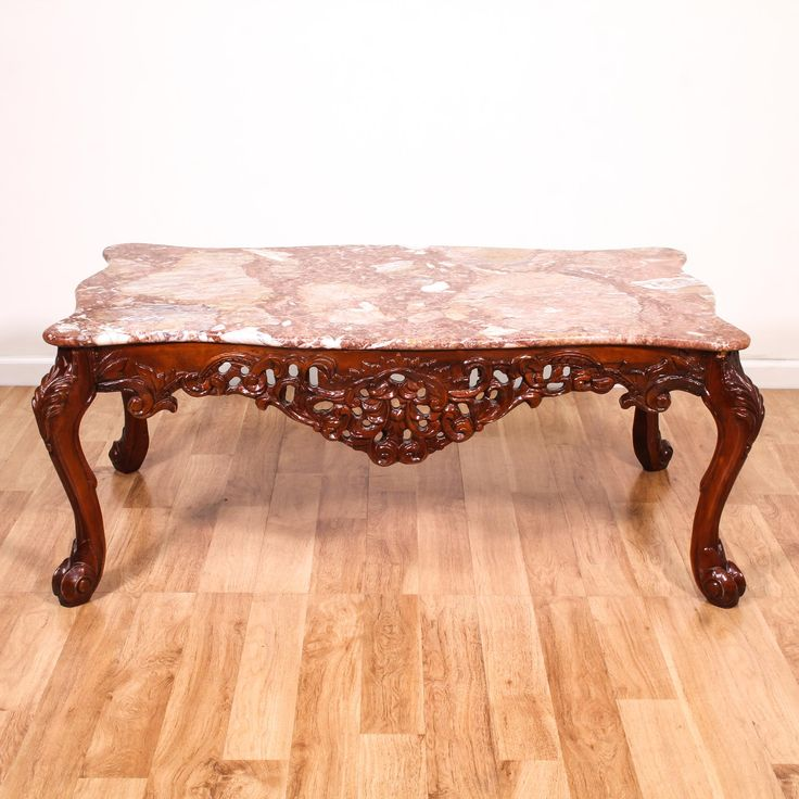 This coffee table is featured in a solid wood with a glossy cherry finish. This victorian table is in good condition with a gorgeous pink and white marble top, curved legs and intricate carved floral details. Unique statement piece perfect for spicing up a space! #europeaninspired #tables #coffeetable #sandiegovintage #vintagefurniture