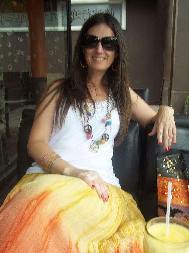 New Hippie Chic : Blusa de algodón con puntilla crochet, falda larga de bambula batik, colgante con pompones multicolores y símbolos de la paz, aros haciendo juego. Pulseras multicolor, bolso batik con mostacillas y lentejuelas.