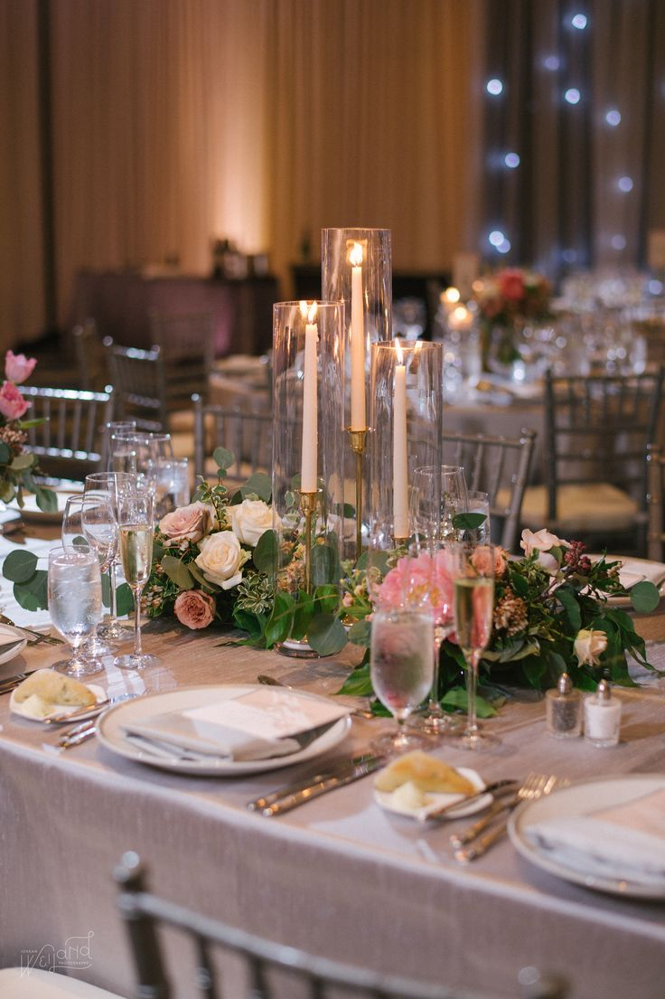 trio of taper candles in gold candlesticks is nestled in lush clusters of coral peonies, blush roses, ivory roses, pink tulips, peach stock, ivory spray roses, rust colored roses, variegated greenery, eucalyptus and greenery on silver table linens.