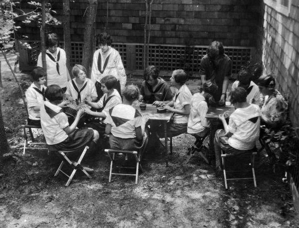 Young girls in school uniforms enjoying an outdoor crafting class. Image ID: 70949