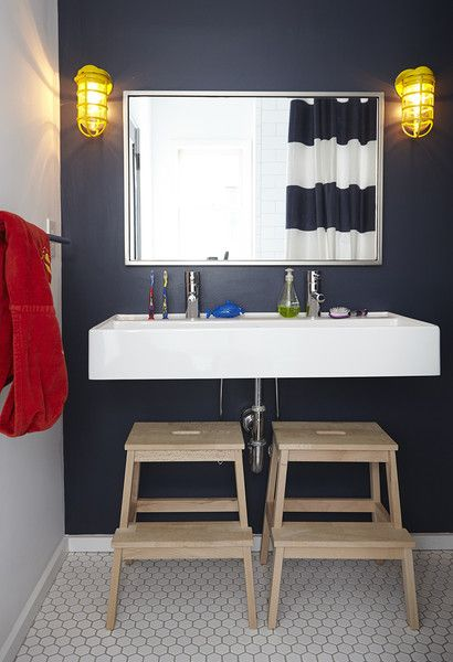 Traditional Bathroom:  A floating white sink in the kids' bathroom is made accessible by two IKEA step stools. .