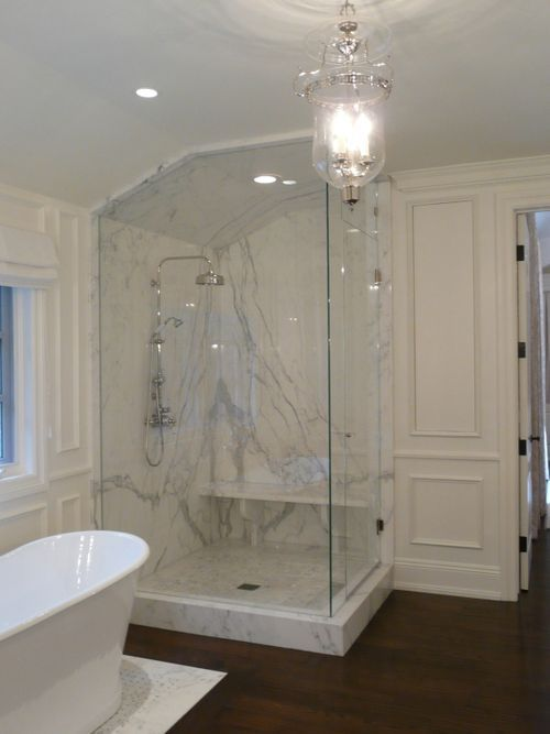 Calcutta marble bathroom with glass shower surround, Vaughan bell jar ceiling light, and dark wood floors.