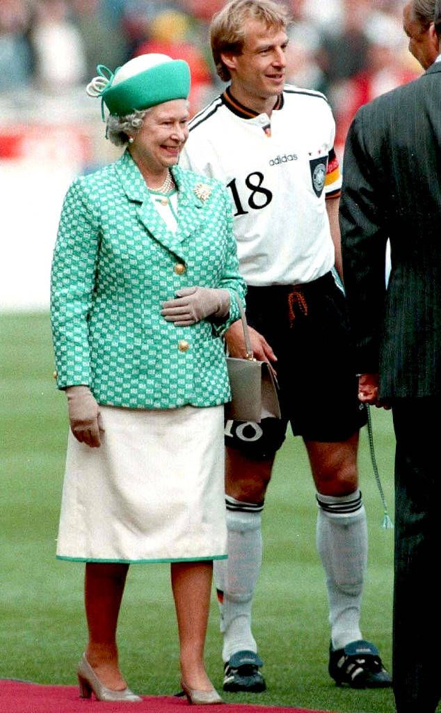 QUEEN ELIZABETH II'S ROYAL STYLE THROUGH THE YEARS 1996 Queen Elizabeth II was all smiles as she stepped out onto a football field in a teal coat, teal-trimmed white skirt and matching hat.