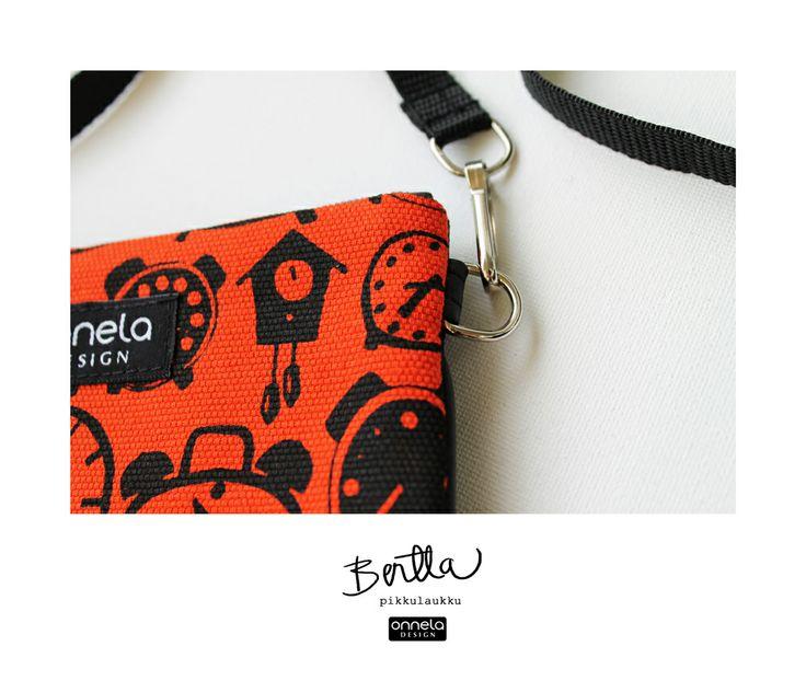 Onnela Design oranssi Bertta-pikkulaukku kellokuosilla. Valmistettu Suomessa, käsinpainettua puuvillaa.