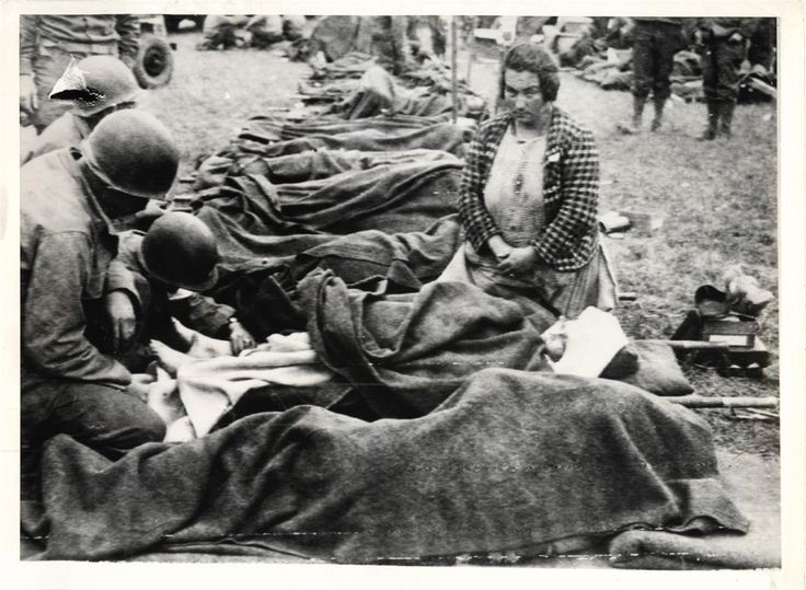 1944- While her mother watches, a young French girl is treated for wounds from German shell fire at an American field hospital in Carentan, France.