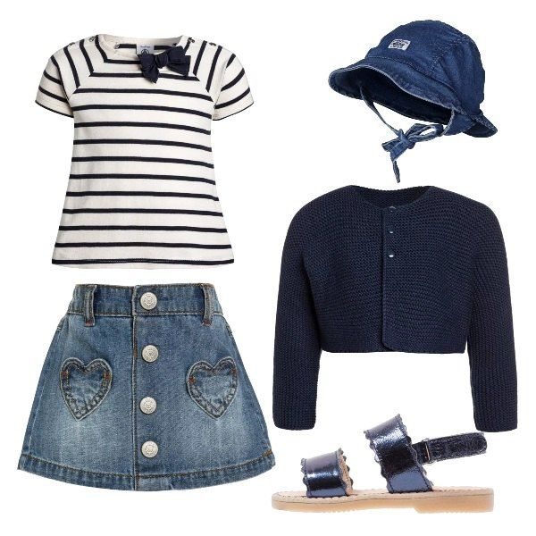 L'outfit della nostra piccola è composto da un cardigan blu con tre bottoni, una t-shirt a righe con fiocco sullo scollo ed una gonna a trapezio in jeans con tasche a toppa. Il look si completa con un berretto con laccetti in jeans ed un paio di sandali in pelle.