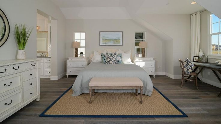 White nightstands flank a cream upholstered bed covered in lovely blue-gray linens in this coastal master bedroom. A natural fiber rug softens the weathered wood floors, and a charming white dresser coordinates with the nightstands. The overall look is calming, relaxing and inviting.