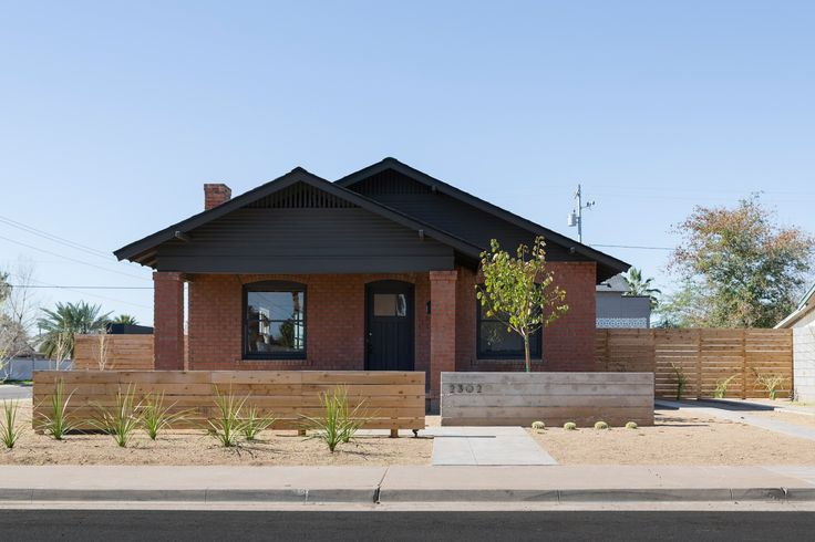 House's east-facing façade refreshed by painting the trim a bold black that echoes the steel addition at the rear.