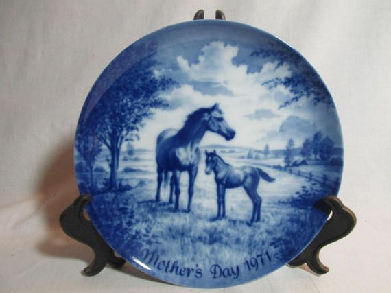 In this 1971 Mothers Day plate shows a mother horse with her baby foal/colt. The 7¾ plate is done in blue and white. The back of the plate says Kaiser and made in West Germany, first issue 1971 with a limited number in the series. It also has a pair hole for the hanging wire. The plate is in excellent condition.