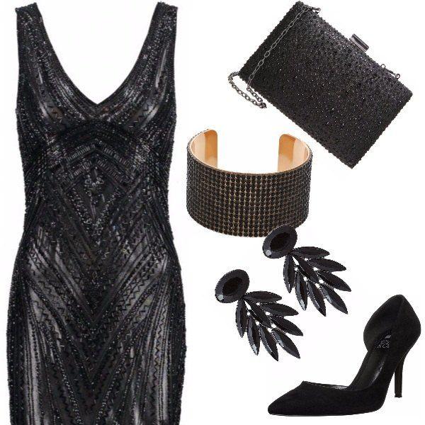 Vestito nero di strass, aderente. Strass anche per la pochette, scarpe con tacco nere, molto semplici, orecchini carinissimi a forma di foglia. Per serate scintillanti!
