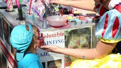 Artist paints on children's faces.