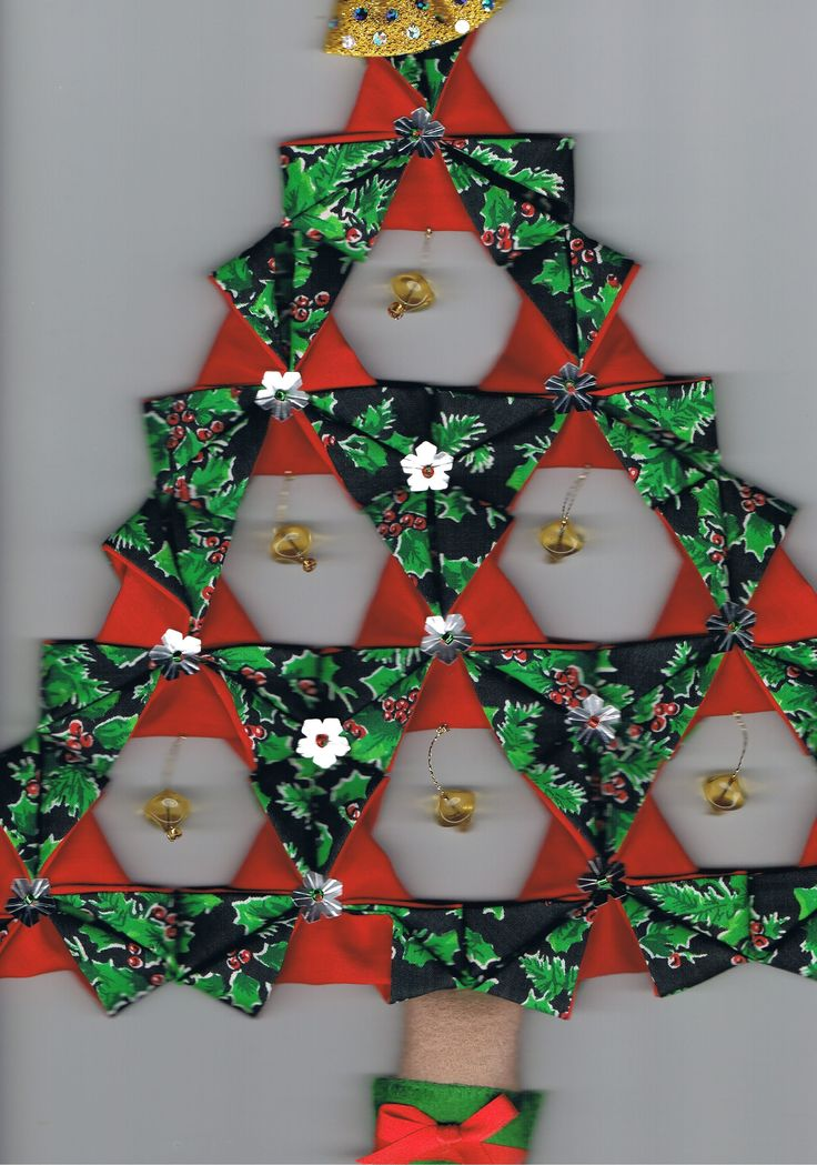 Folded patchwork Christmas tree Start with triangles with red on one side and Xmas fabric on the other.  With red facing you, fold each corner into the middle and secure with a sequin.  Sew them together to form the tree.