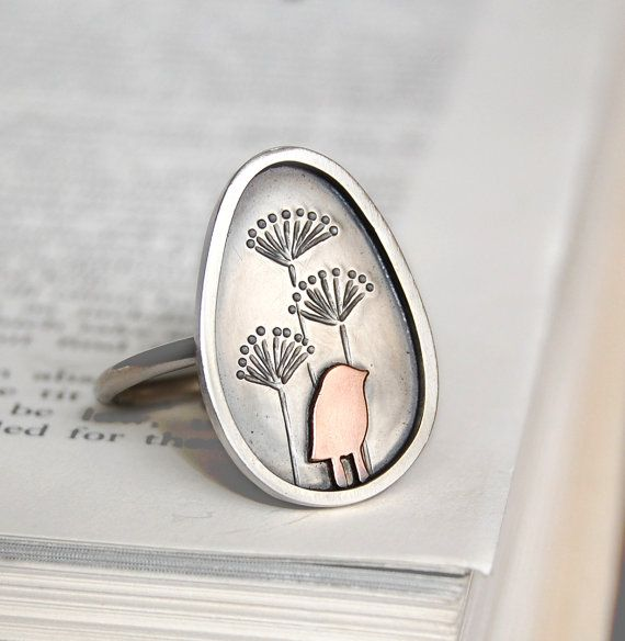 This handmade sterling silver ring depicts a tiny copper bird standing in front of some seed heads. The bird is hand cut from copper, and then