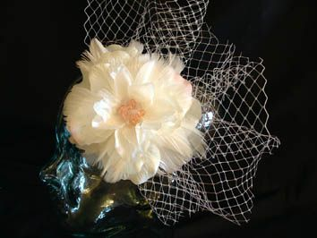 A silk flower, feathers veiling and peach crystals as a centre.