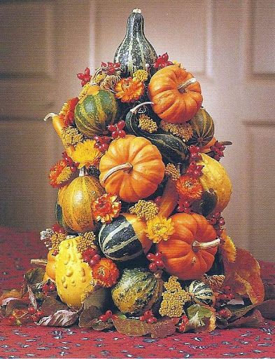 Williamsburg Fall Pumpkin Centerpiece: Colorful gourds and mini-pumpkins arranged in a tandom pattern are accented with yarrow, strawflowers, and dogwood berries.  Consists of cone-shaped wooden form 10 inches high, 5 inches wide at the base, and 2 1/2 inches wide at the top (available through Colonial Williamsburg), mini pumpkins or gourds, strawflowers, and dogwood berries for filler