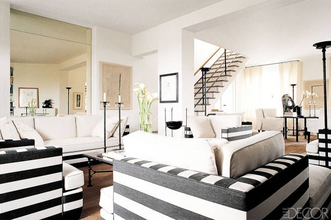 A PARIS LIVING AREA  Frédéric Méchiche employed his signature motif of graphic black and white when designing canvas upholstery for the living area of a Paris duplex. The cocktail table holds wrought-iron candlesticks of his own design.