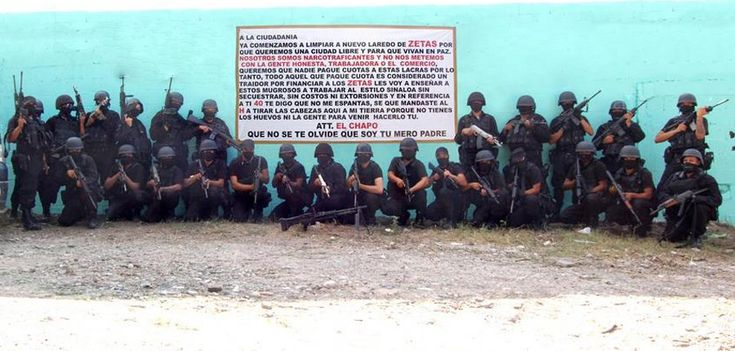 Gunmen associated with the Sinaloa Cartel pose in front of a sign threatening the Los Zetas Cartel.