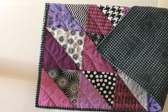 The Sean design is created with colorful purple triangles in an attractive pattern pleasing to babies, children or adults! This quilt measures 36 x 42 inches. The binding and backing is made with a black and gray dotted fabric. Dont hesitate to enjoy this quilt in a variety of settings. Easy to bring along wherever you go, it is a great size for carriage or crib, and can also be used as a play mat or wall hanging. Lightweight yet warm and cuddly, this quilt could easily become a childs…